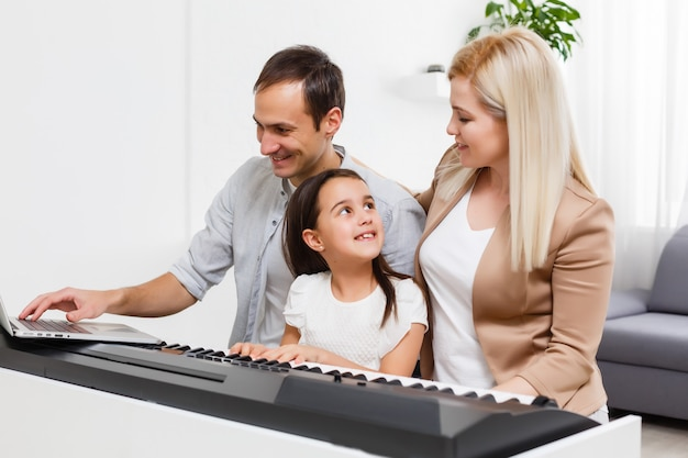 Gelukkige familie, moeder, vader en dochter thuis piano spelen, concept voor familierelatie. muziekschool en muziekfamilie.