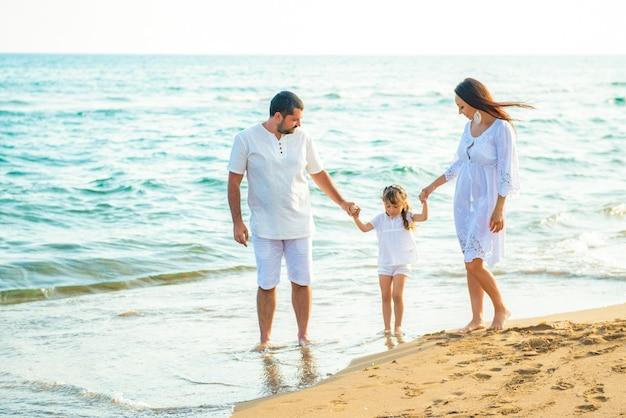 Gelukkige familie moeder, vader en dochtertje lopen langs de kust op zee strand in het resort.