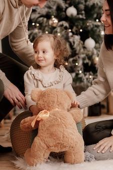 Gelukkige familie, moeder, vader en dochtertje met teddybeer in de buurt van kerstboom en open haard thuis.