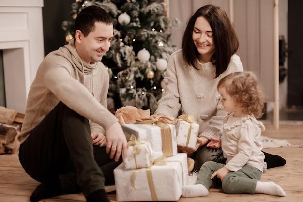 Gelukkige familie, moeder, vader en dochtertje met veel cadeautjes dozen in de buurt van de kerstboom en open haard thuis.