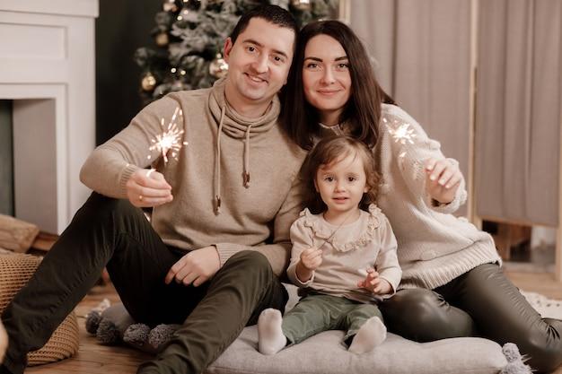 Gelukkige familie, moeder, vader en dochtertje met wonderkaarsen in de buurt van kerstboom en open haard thuis.