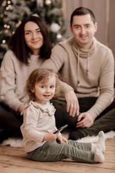 Gelukkige familie, moeder, vader en dochtertje spelen met mobiel en zitten in de buurt van de kerstboom thuis.