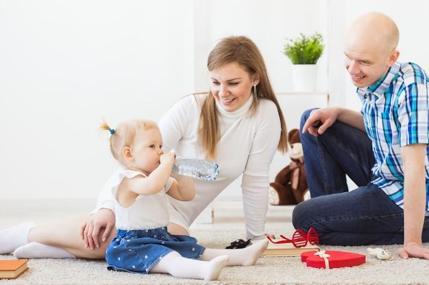 Gelukkige familie, moeder, vader en hun baby die samen in huiskamer spelen. kinderen en