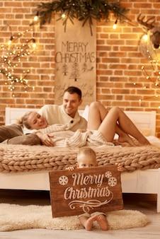 Gelukkige familie moeder vader en kind op kerstochtend in de slaapkamer spelen en plezier hebben
