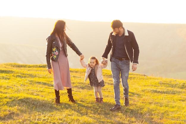 Gelukkige familie, moeder, vader en kinddochter op aard op zonsondergang