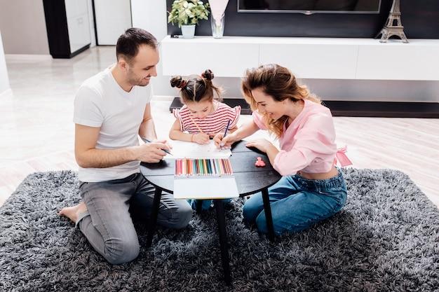 Gelukkige familie, moeder, vader en kinderen tekenen samen thuis.