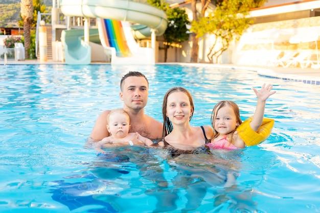 Gelukkige familie moeder, vader en twee kinderen zwemmen in het zwembad met glijbanen en hebben plezier op vakantie, glimlachen en lachen
