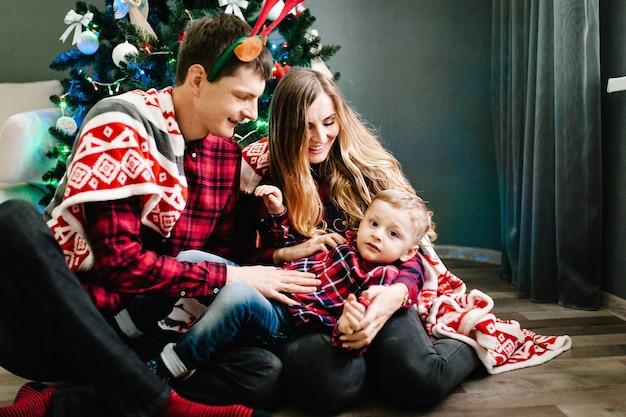 Gelukkige familie moeder, vader en zoon in de buurt van de kerstboom met geschenken en open haard.