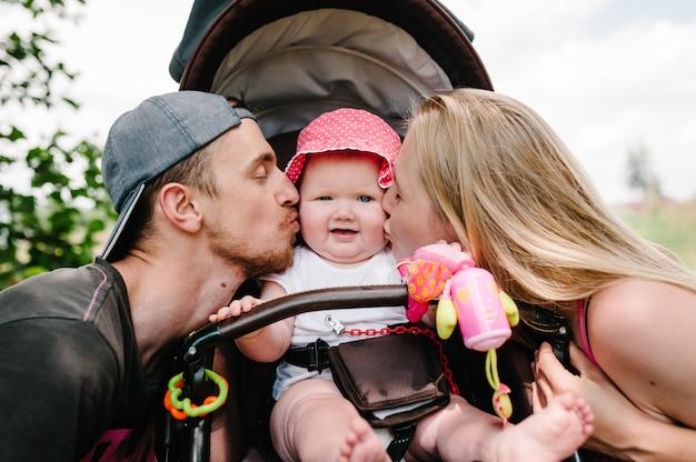 Gelukkige familie: moeder, vader kussen meisje in kinderwagen.