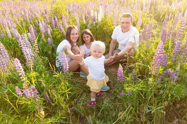 Gelukkige familie moeder vader omarmen kinderen buiten. vrouw man baby kind en tienermeisje zittend op zomer veld met bloeiende bloemen achtergrond. gelukkige familie moeder vader en dochters spelen op weide.