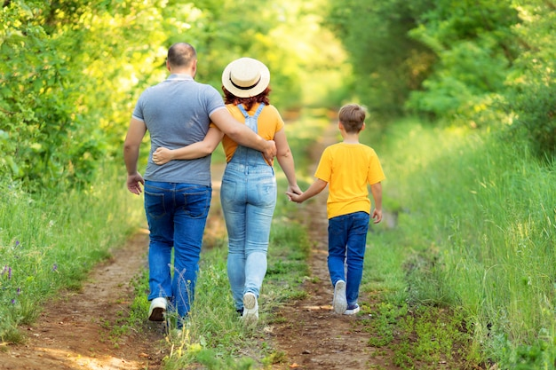 Gelukkige familie, moeder, vader, zoon lopen, hand in hand buiten in de zomer. achteraanzicht