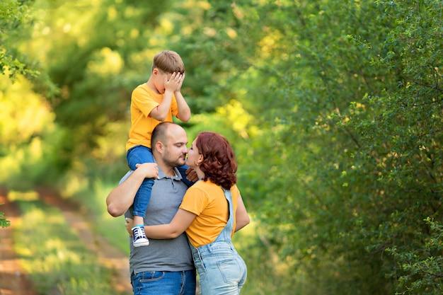 Gelukkige familie, moeder, vader, zoon lopen, knuffelen, kussen elkaar op straat in de zomer