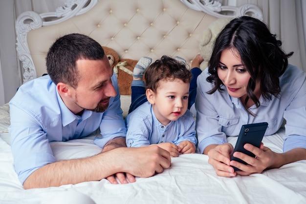 Gelukkige familie mooie moeder zoontje en vader kijken cartoon in telefoon liggend op bed in slaapkamer