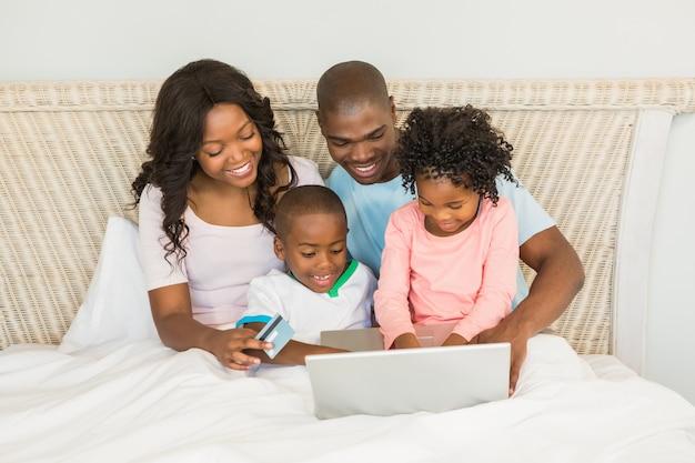Gelukkige familie online winkelen met laptop