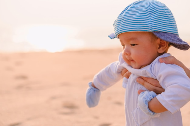 Gelukkige familie ontspannen aan zee. gelukkige familie rusten op het strand in de zomer. moeder met babyjongen die op het strand rust.
