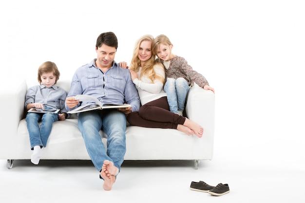 Gelukkige familie op bank die op wit wordt geïsoleerd