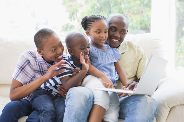 Gelukkige familie op de bank die met laptop babbelt