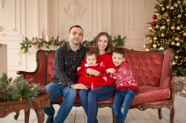Gelukkige familie op de bank in de buurt van de kerstboom