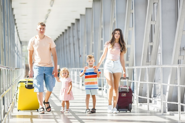 Gelukkige familie op de luchthaven met koffers reizen Premium Foto