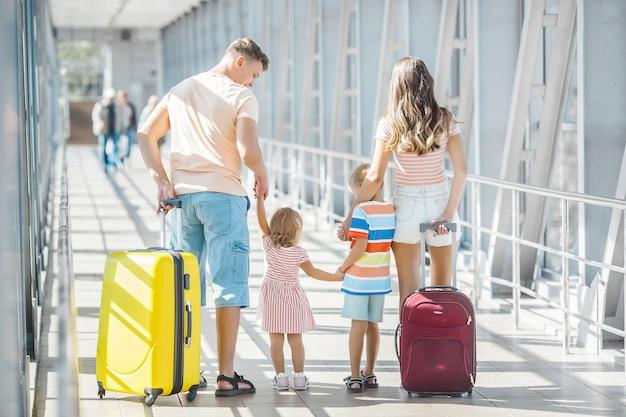 Gelukkige familie op de luchthaven met koffers reizen