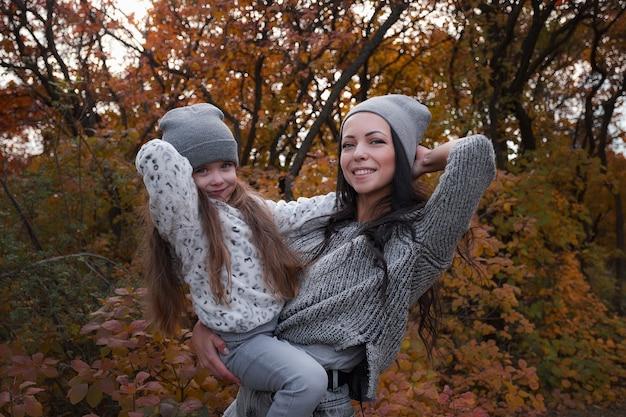 Gelukkige familie op een herfstwandeling. moeder en dochter wandelen in het park en genieten van de prachtige herfstnatuur.