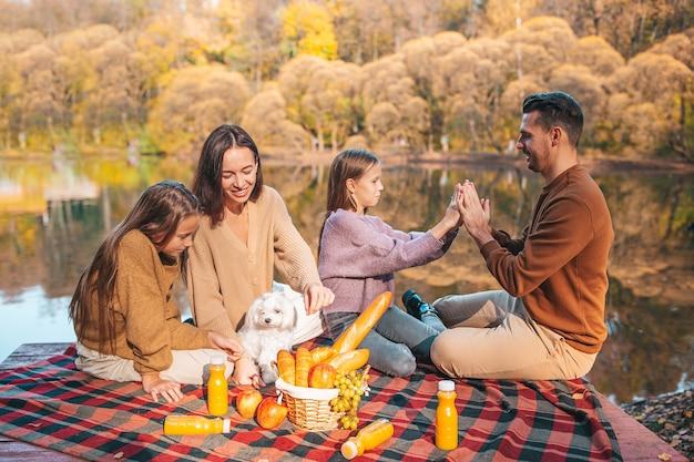 Gelukkige familie op een picknick in het park in de herfst