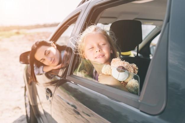 Gelukkige familie op een road trip in hun auto. vader, moeder en dochter reizen door de zee of de oceaan of de rivier. zomerrit met de auto