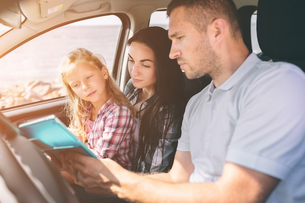 Gelukkige familie op een road trip in hun auto. vader, moeder en dochter reizen langs de zee of de oceaan of de rivier. zomerrit met de auto