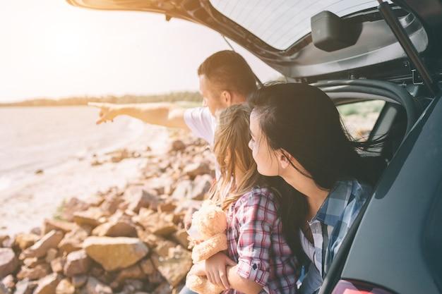 Gelukkige familie op een roadtrip in hun auto. vader, moeder en dochter reizen door de zee of de oceaan of de rivier. zomerrit met de auto.