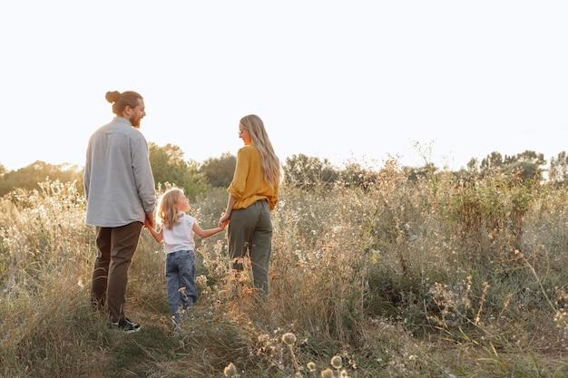Gelukkige familie op een wandeling samen bij zonsondergang. kinderbescherming