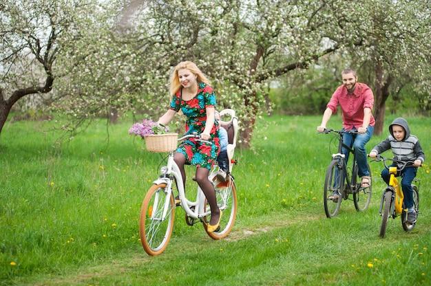 Gelukkige familie op fietsen in de de lentetuin