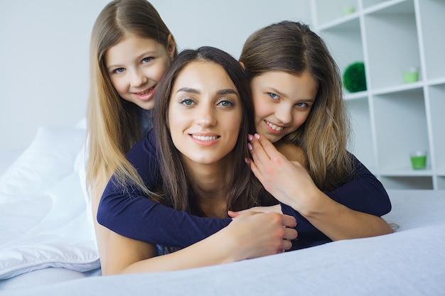 Gelukkige familie op het bed. kinderen met hun moeder in de slaapkamer.