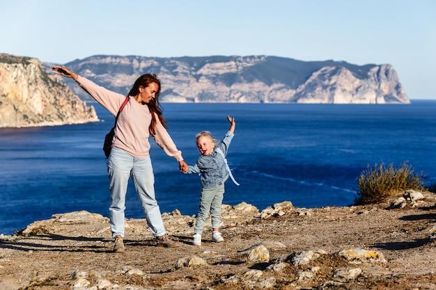 Gelukkige familie op het strand mensen plezier op zomervakantie moeder en kind tegen blauwe zee