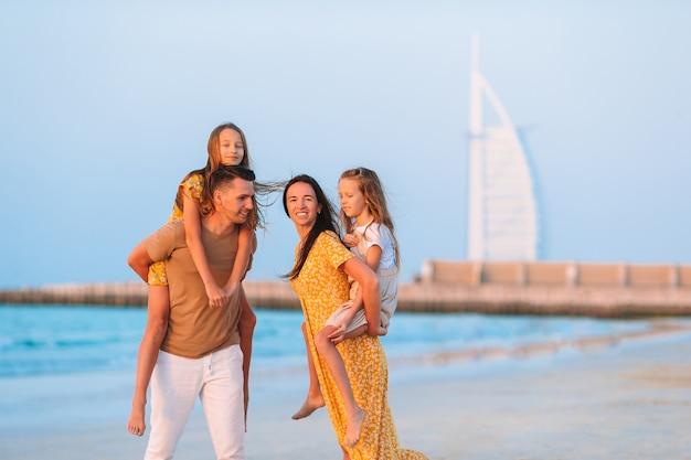 Gelukkige familie op het strand op zomervakantie met burj al arab in dubai, verenigde arabische emiraten.