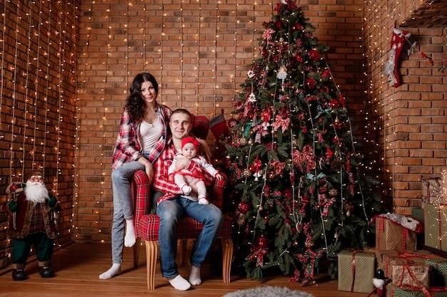 Gelukkige familie op kerstavond zitten samen in de buurt van versierde boom in de woonkamer, thuis. vader, moeder en babymeisje.