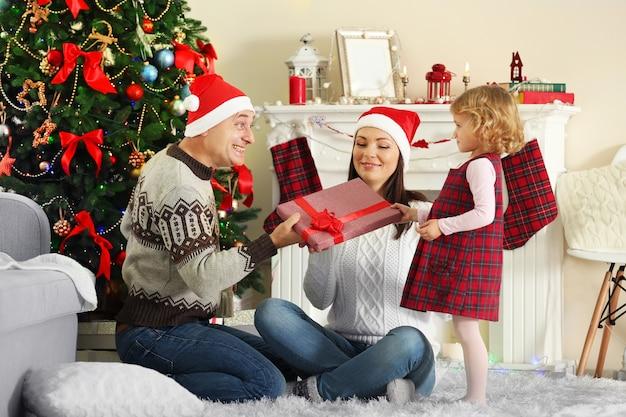Gelukkige familie op kerstboom. dag uitpakken