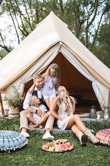 Gelukkige familie op picknick, zittend op groen gras in de buurt van de grote witte tipitent in bos of park