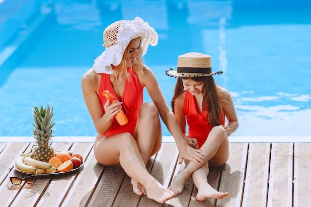 Gelukkige familie op vakantie. moeder en dochter in zwemkleding die bij het zwembad zitten.
