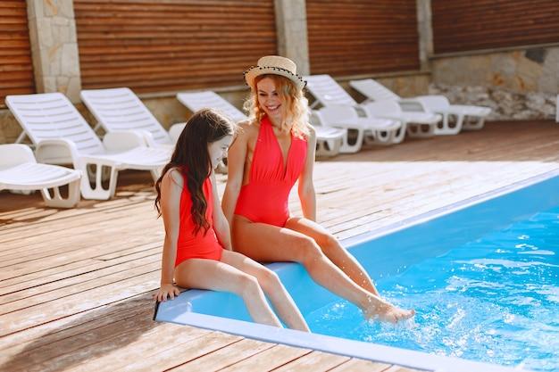 Gelukkige familie op vakantie. moeder en dochter in zwemkleding en zonnebril die bij het zwembad zitten.
