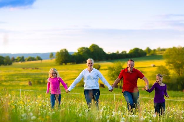 Gelukkige familie op weide bij zonsondergang