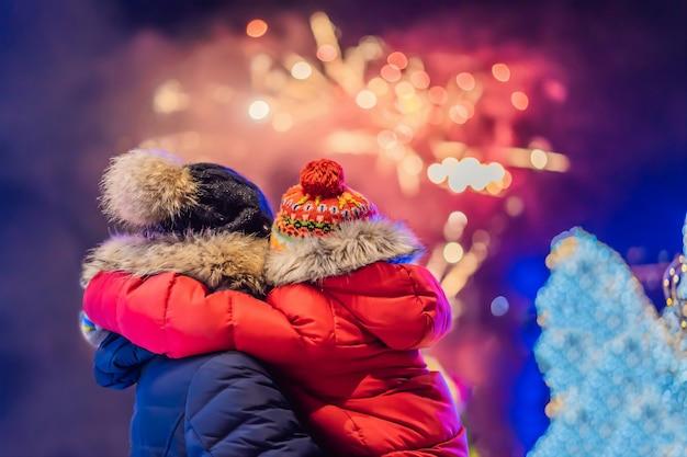 Gelukkige familie op zoek vuurwerk in de avondlucht