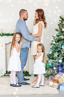 Gelukkige familie ouders knuffelen met hun dochters bij de witte open haard met elegante kerstboom