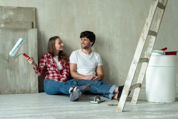Gelukkige familie paar ontspannen na schilderij jong koppel liggend op de vloer van een nieuw huis en met elkaar communiceren