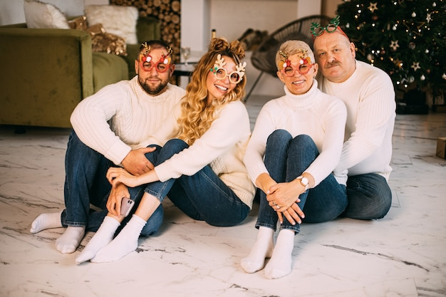 Gelukkige familie partij bril en zittend op de vloer naast mooi versierde kerstboom