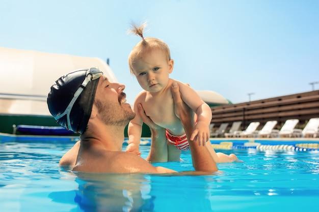 Gelukkige familie plezier bij het zwembad.