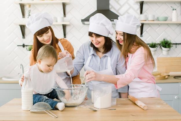 Gelukkige familie plezier in de keuken. grootmoeder en haar dochters en klein meisje kneden deeg samen in de keuken thuis. gelukkige moederdag, familie koken