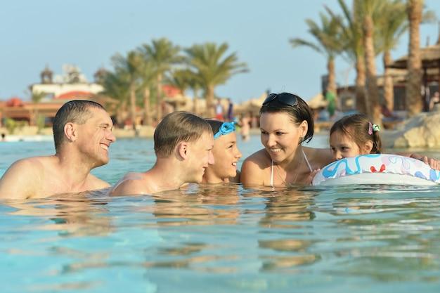 Gelukkige familie plezier in zwembad met duimen omhoog
