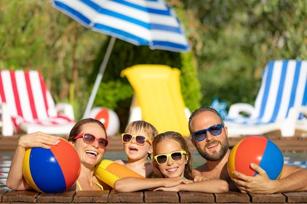 Gelukkige familie plezier op zomervakantie. vader, moeder en kinderen spelen in zwembad. actief gezond levensstijlconcept