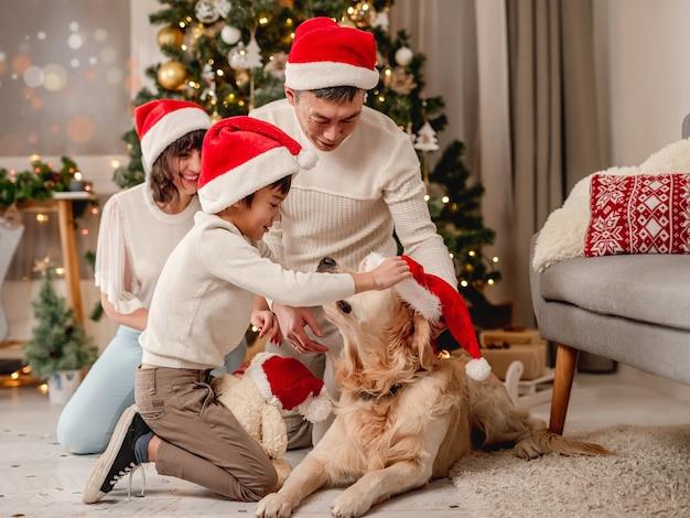 Gelukkige familie poseren in de buurt van kerstboom terwijl golden retriever hond langskomt voor de camera