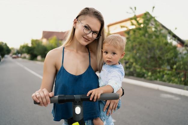 Gelukkige familie rijden scooter in de buurt op de weg.